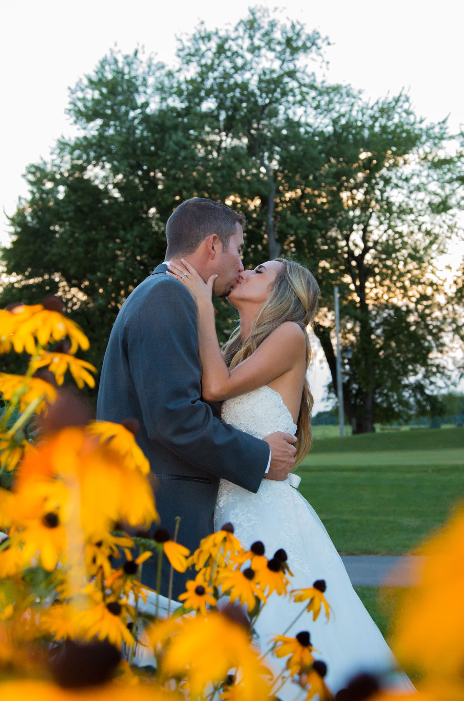 Webster, NY Wedding bride kisses groom by flowers