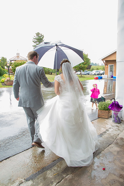 bride and groom in the rain under an umbrella