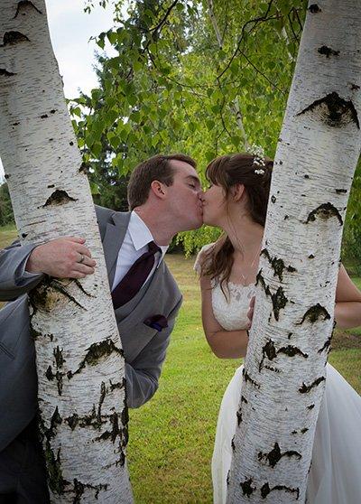 bride and groom kiss behind a tree