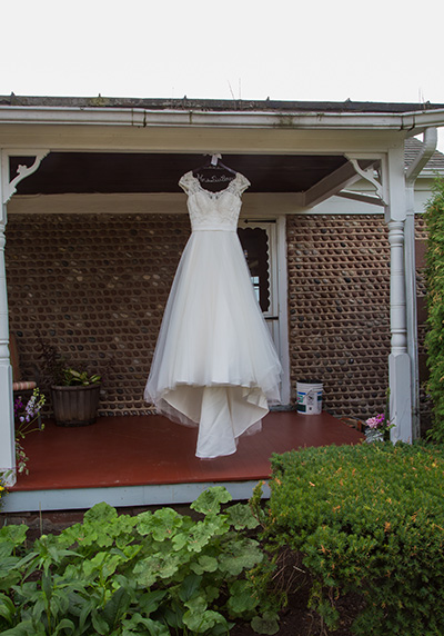 wedding dress hangs from a country porch