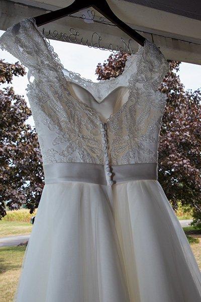 wedding dress hangs from a porch
