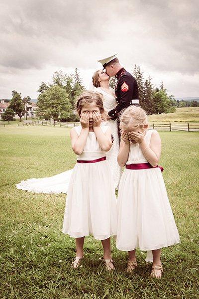 bride groom kiss in front of bashful flower girls