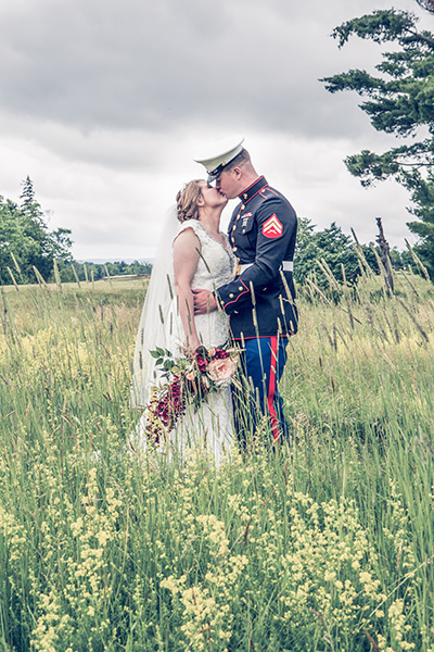 bride kisses her marine among the weeds