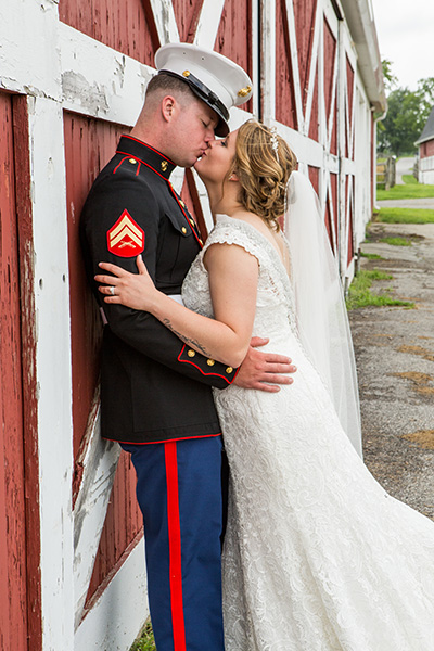 bride kisses her groom on a barn