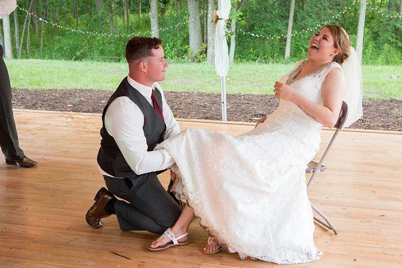 groom gets bride's garter at the reception