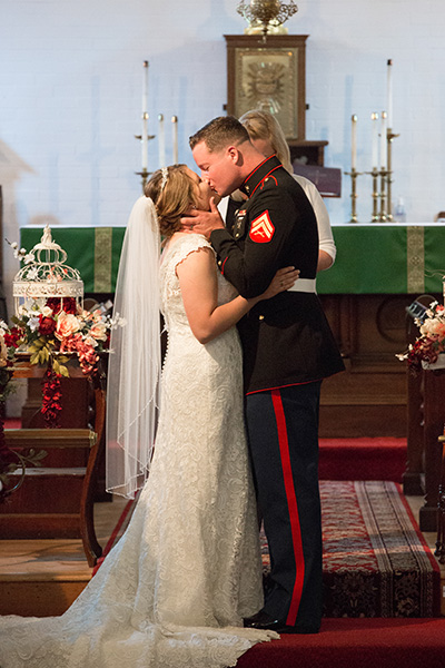marine kisses bride at the alter