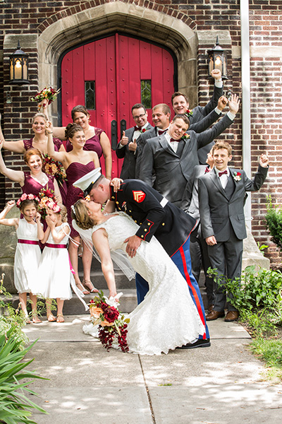 marine dips and kisses his bride as bridal party cheers on