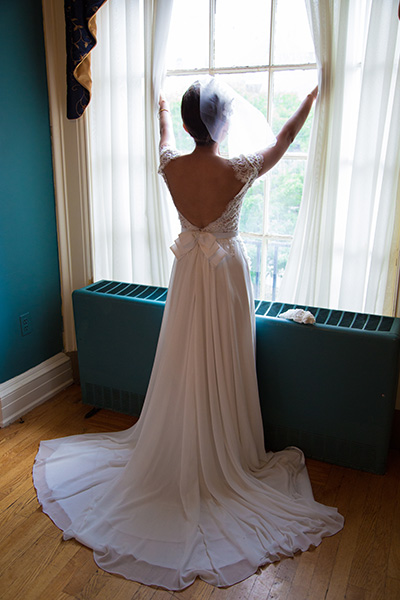 bride opens curtains to look outside