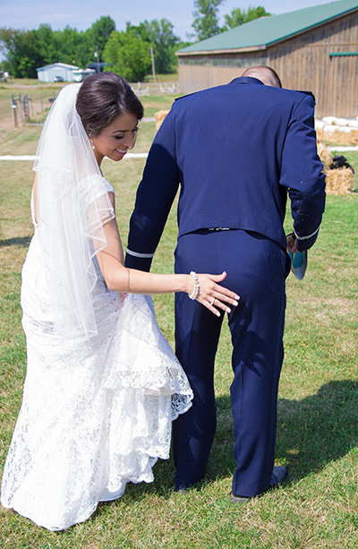 bride brushes her groom's butt