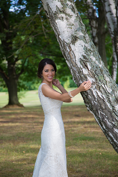 bride pose next to a tree