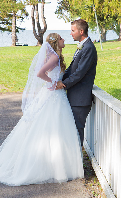 bride and groom kiss along a fence