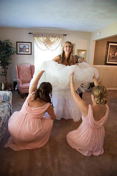 bridesmaids working on the wedding dress