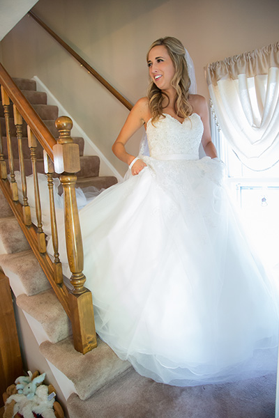 bride in dress coming down the stairs