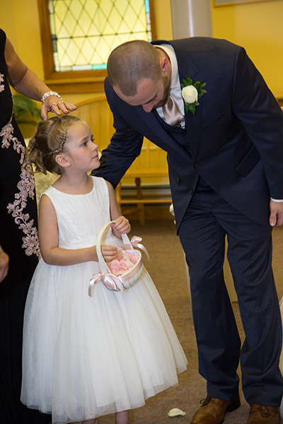 groom gets advice from the flower girl