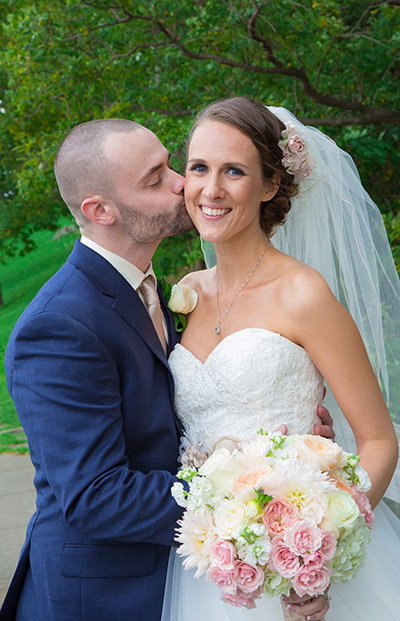 groom kisses his bride on the cheek