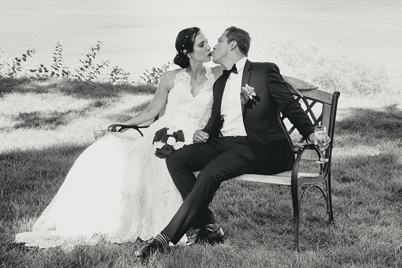 bride and groom kiss on a bench