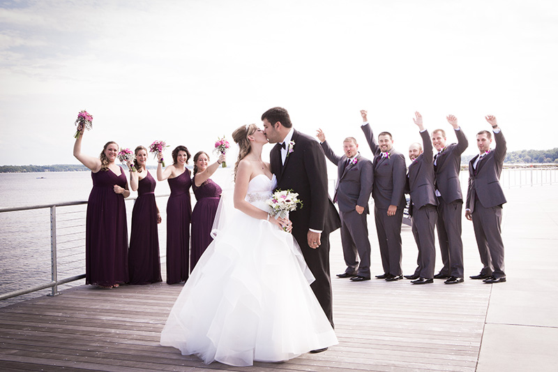 bride and groom kissing with bridal party watching