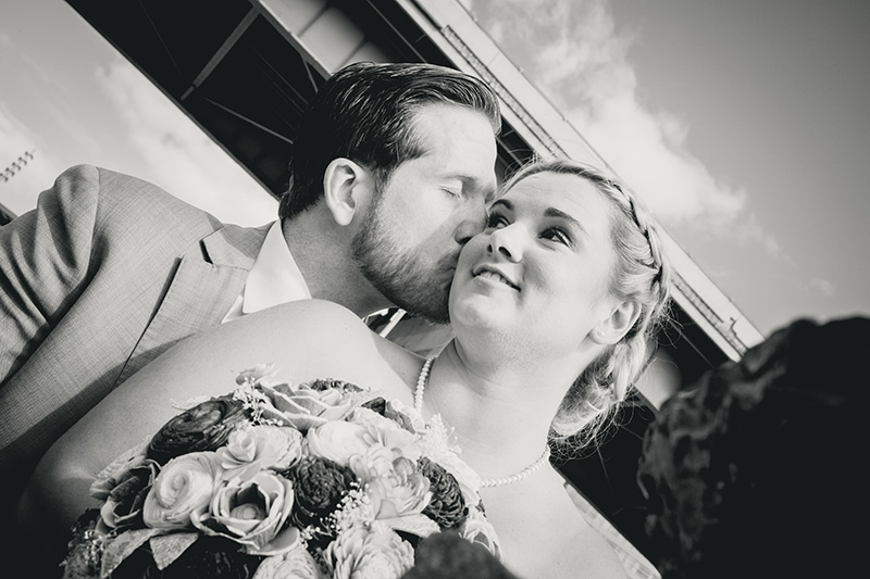 groom kisses his bride on the cheek