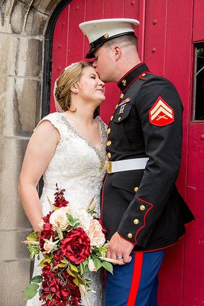 groom kisses bride in front of church door