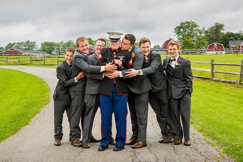 groom hugged by his groomsmen