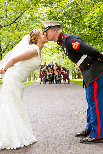 bride groom kiss with bridal party in the background