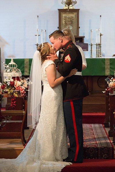 marine kisses bride at the alter