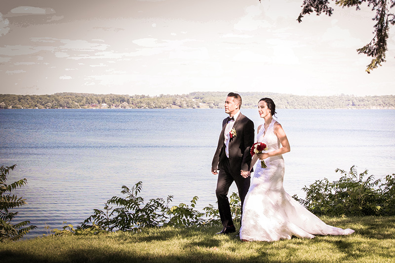 bride and groom walking by a lake