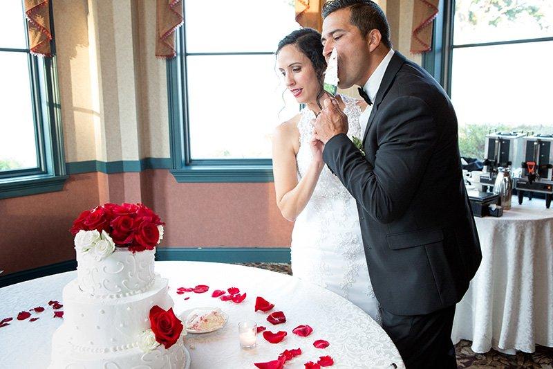 groom licks the wedding cake knife