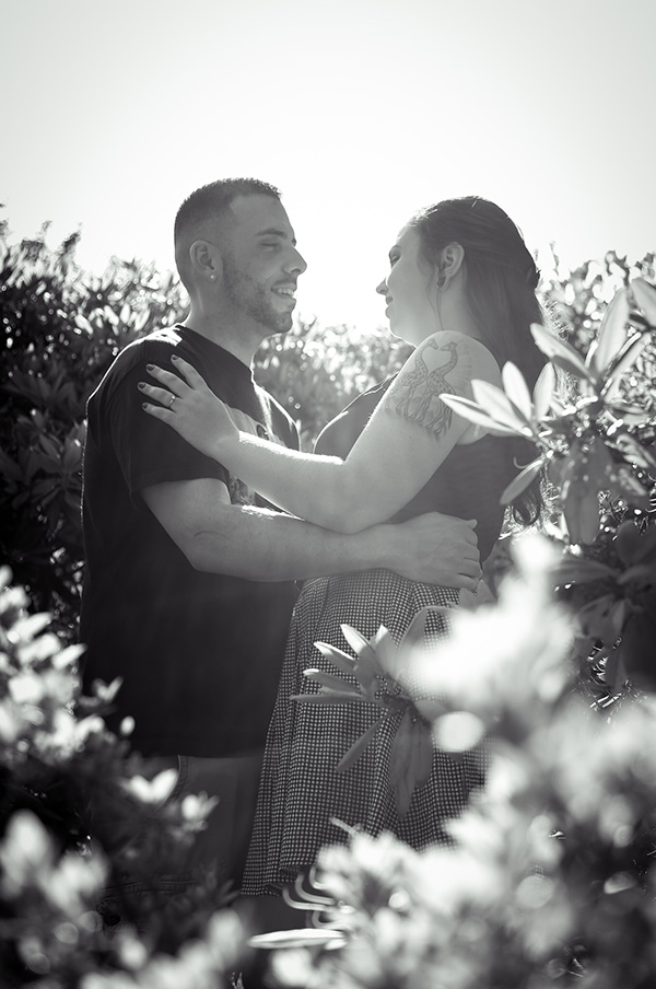 couple embrace with the sun behind them